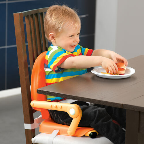 Young boy eating at the table with the Chicco Pocket Snack Booster Seat