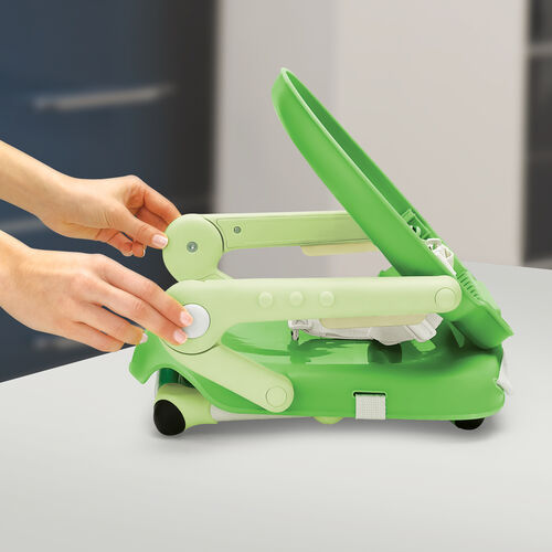 Press the backrest release buttons to fold the Pocket Snack Booster Seat