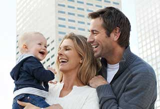 family with baby smiling about the Chicco Brand