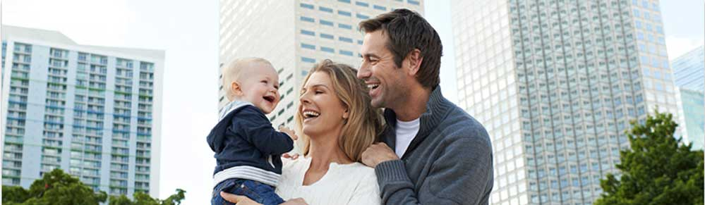 smiling mother and father with baby against city background emulating the Chicco brand